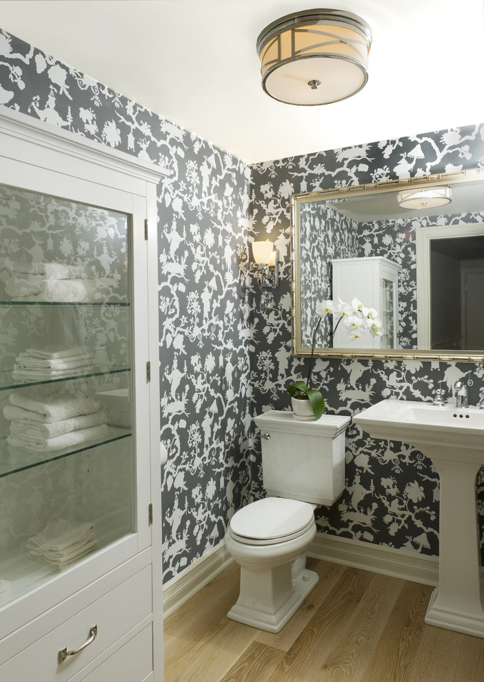 polished nickel mirror wooden floor toilet white freestanding sink wall sconces black and white wallpaper ceiling light white cabinet glass shelves