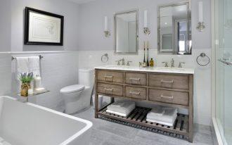 polished nickel mirror wooden vanity white granite countertop double sink wall sconces glass shower doors grey floor tile white acrylic bathtub toilet shower holder white su