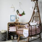 Rattan High Baby Cot With Pink Cushion In A Nursery With White Wall, Shelves, Fur Rug