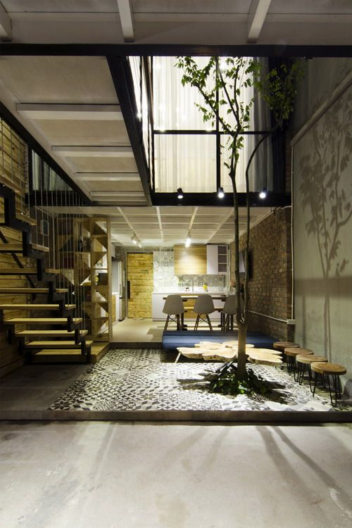 small space near kitchen with pattern tiles, small spaceto grow a tree, wooden chars, table, long blue bench
