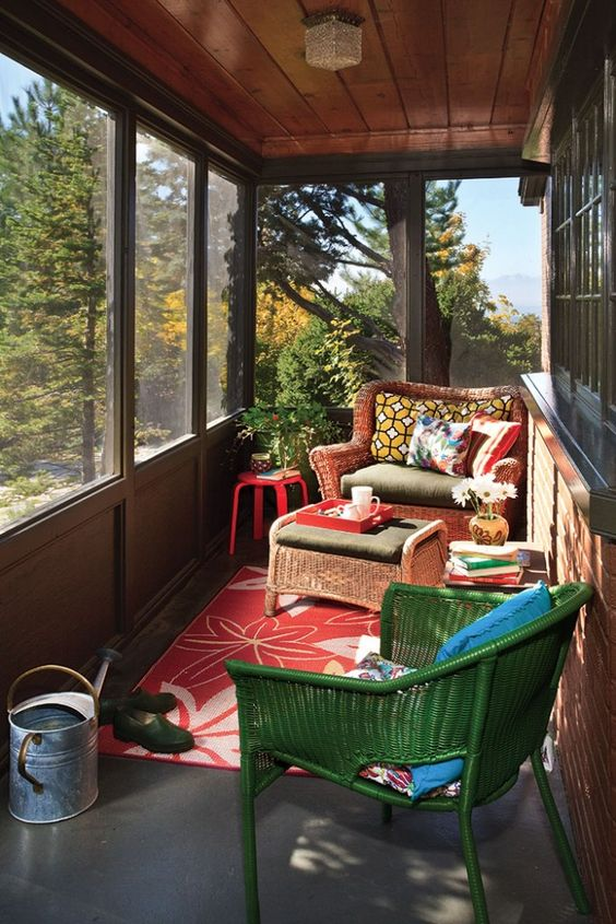 sun room with grey floor, brown wooden wall and ceiling, brown bricks wall, red rug, green rattan chair, brown rattan sofa with ratta coffee table