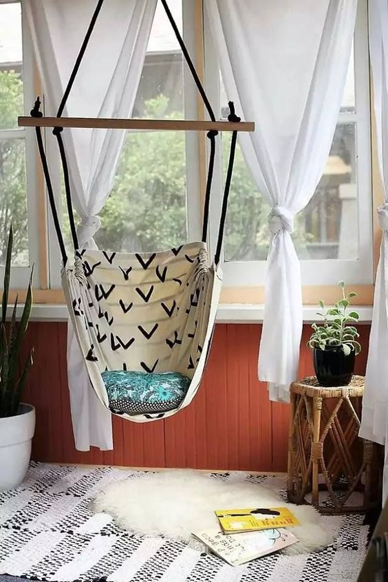 swing with cotton cloth, rope, and wooden support installed from the ceiling near the window with white curtain