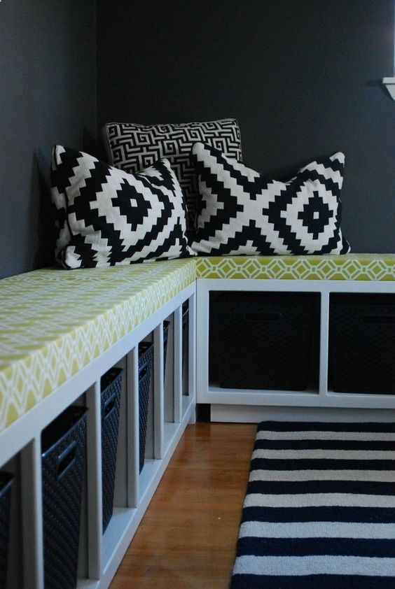 white bench with shelves below, green cushion, black and white pillows