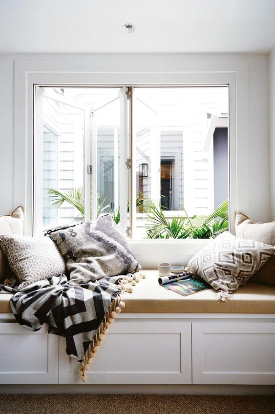 white wooden reading nook with storage inside, brown cushion, pillows
