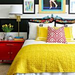 Bedroom With Black And White Striped Wall, Beige Rug, Red Cabinet, Colorful Bedding, White Table Lamp