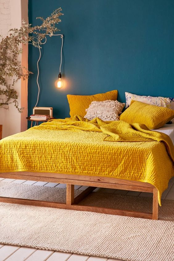 bedroom with turquoise wall, beige wall, wooden floor, beige rug, white bed, yellow pillows and blanket