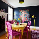 Dining Room With Dark Blue Wall, Wooden Floor, Yellow Table, Purple Chairs, Yellow Floor Lamp, White Fireplace, Black Ceiling Lamp