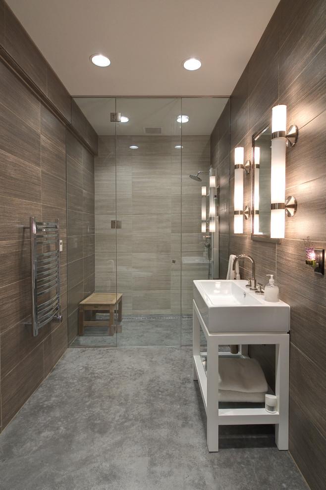 frameless shower door sweep brown walls tiles white freestanding vanity white sink wall sconces wall mirror wooden bench shower fixture