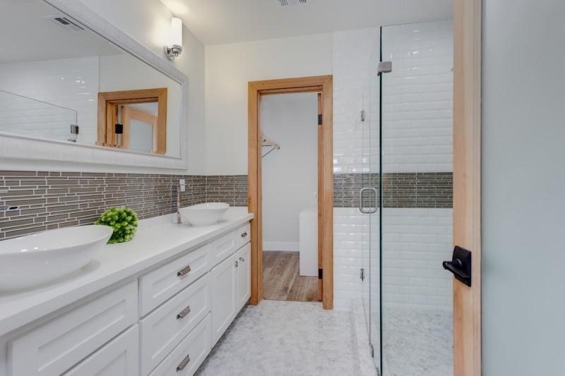 frameless shower door sweep grey subway tile white wall tile marble flooring wooden doors white vanity white sink bowl wall mirror wall sconces