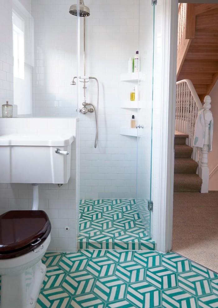frameless shower door sweep patterned floor tile toilet built in shelves white walls tiles shower fixtures window white window shade