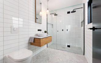 frameless shower door sweep wall mounted head shower white walls tiles herringbone floor tile pendant lamp wall mirror wall mounted wooden cabinet white sink wall moun