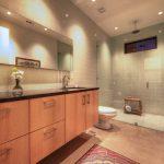 Frameless Shower Door Sweep Wooden Floating Vanity Black Countertop Wall Mirror Green Tiled Walls Brown Floor Tile Bathroom Rug Rainfall Shower Head