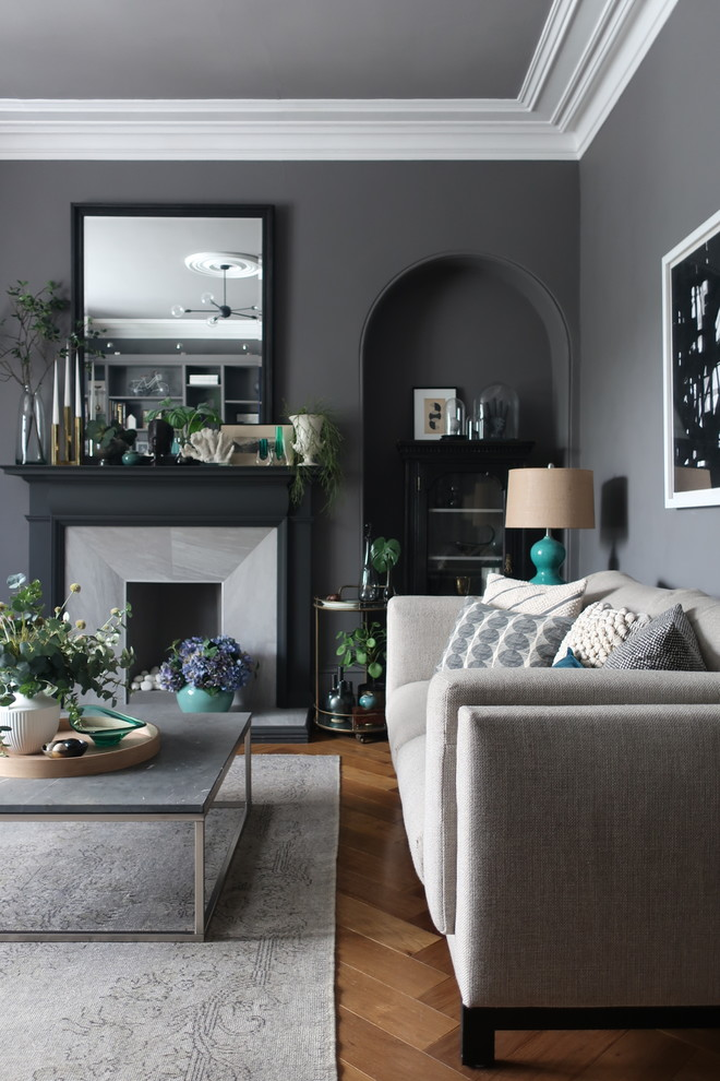 gray table fireplace grey sofa pillows grey rug wooden herringbone floor tile grey walls cabinet wall mirror tosca table lamp black and white wallart chandelier