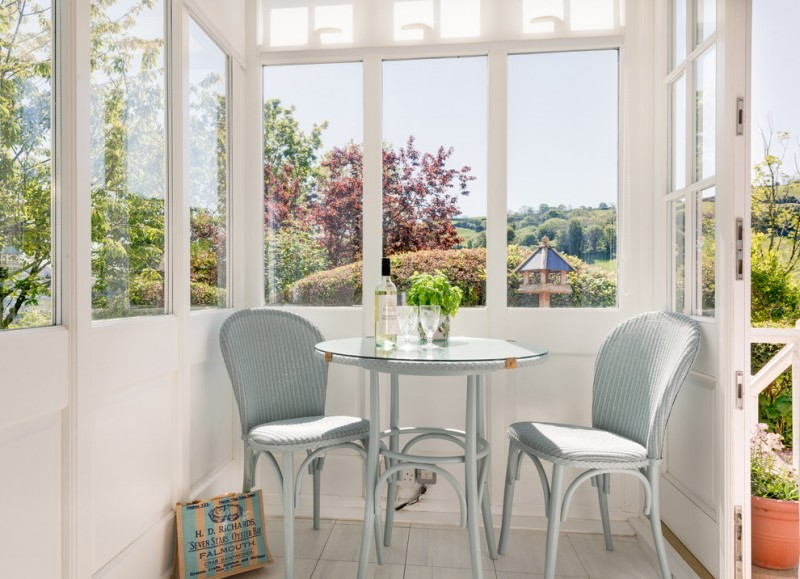 gray table gray dining chairs round glass top big windows white walls white glass doors trees striped grey textured chairs cushions