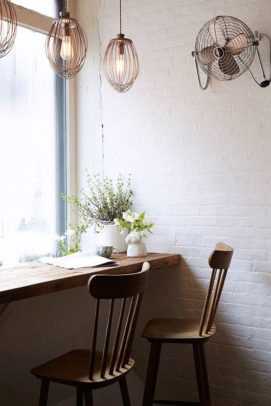 large windows with dark wooden table, slim thin wooden chairs