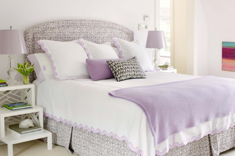 light purple pillows bed with skirt and headboard purple table lamps white side tables purple throw white pillows colorful artwork windows