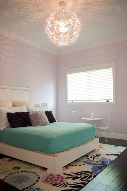light purple pillows chandelier purple walls shag pillows white wooden bed window blinds white chairs table colorful area rug white headboard
