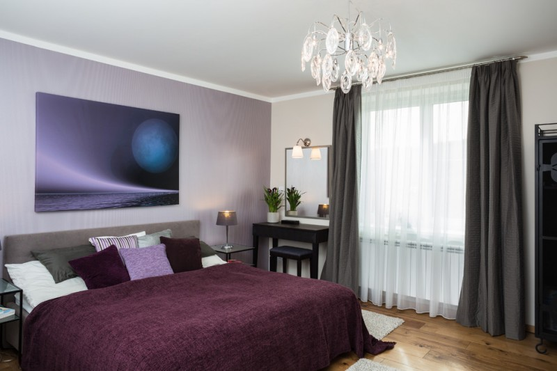 light purple pillows crystal chandelier purple bedding colorful pillows artwork black desk stool wall mirror table lamp wall sconce purple wall wooden floor grey curtains windows