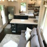 Open Kitchen With Dark Cabinet, White Counter Top, White Wooden Wall, Light Fixture, Living Room With Grey Sofa, Grey Rug, White Ottoman