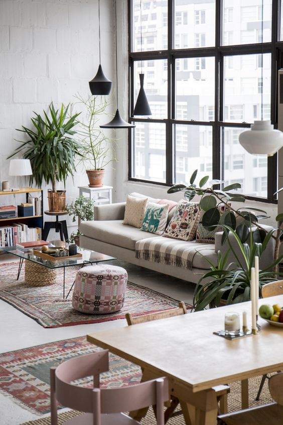 open space with mediterran rug, beige sofa, glass coffee table, wooden shelves, wooden dining set, big windows