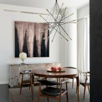 Round Wood Table Top Chandelier Grey Floor Console Wooden Dining Chairs Black Leathered Chairs Cushions Grey Area Rug White Curtains Artwork