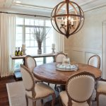 Round Wood Table Top Chandelier Pedestal Dining Table Beige Dining Chairs Wooden Floor Beige Area Rug White Curtains Glass Windows Wall Sconce