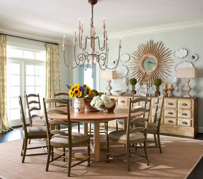 round wood table top chandelier sunburst wall mirror wooden cabinet curtains wooden chairs beige traditional rug whte table lamps white glass doors