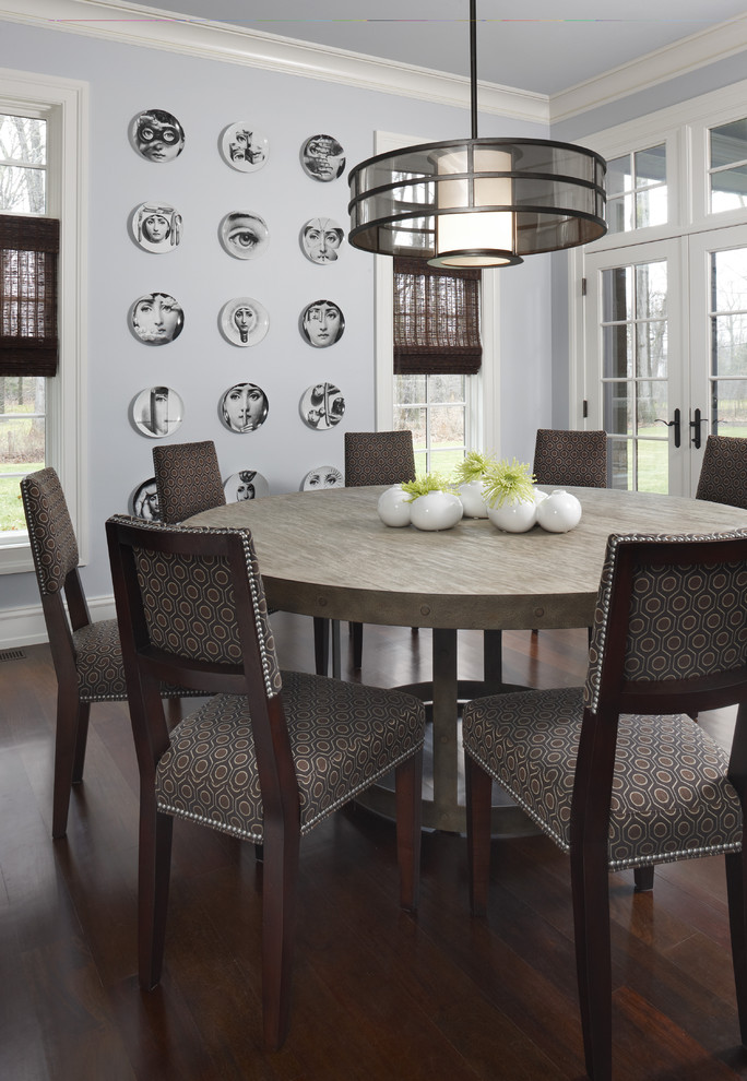 round wood table top chandelier wooden dining chairs wooden floor patterned cushions wallarts white walls glass windows rattan shades french glass doors
