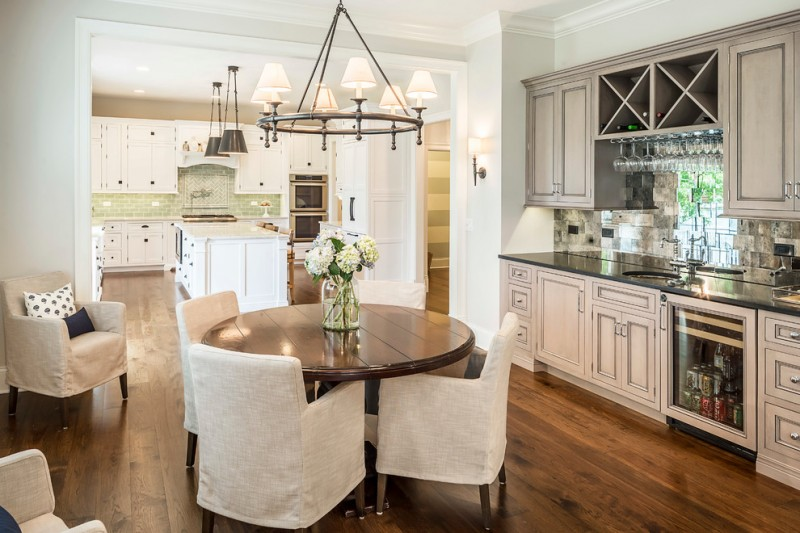round wood table top classic beige dining chairs wooden floor black countertop mirrored backsplash tile chandelier white island pillows