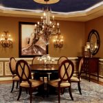 Round Wood Table Top Crystal Chandelier Crystl Wall Sconces Wall Mirror Wooden Chairs Patterned Area Rug Wooden Console Goblets Artwork