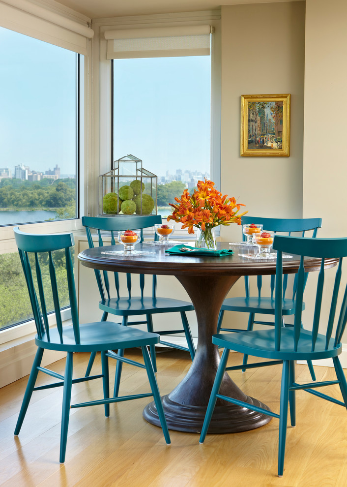 round wood table top wooden blue chairs glass flower vase gold framed wall art glass windows wooden flooring white walls white console wooden pedestal table