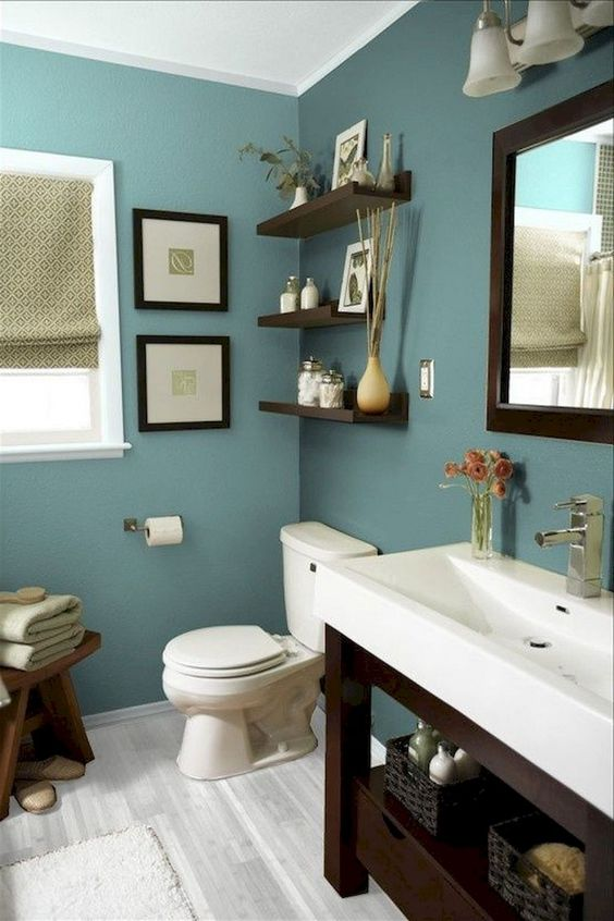 small bathroom with soft dark green painted wall, white sink, brown wooden shelves, mirror, window, curtain, white toilet, wooden stool