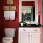 Small Bathroom With White Floor, Red Wall, White Toilet, White Cabinet With Black Marble Top, White Wooden Framed Mirror, White Sconces