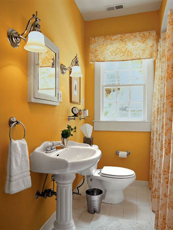 small bathroom with yellow painted wall, white tiles, white toilet, white sink without cabinet, yellow sconces, white framed window, yellow curtain
