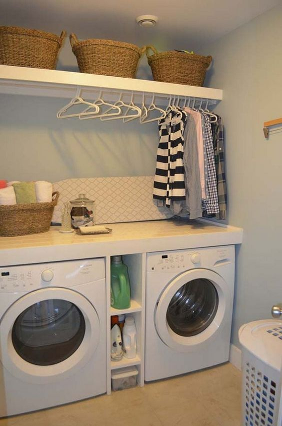 small laundry room with white wall, light brown floor, two machines with shelves between, hangers, ironing table, baskets, laundry basket