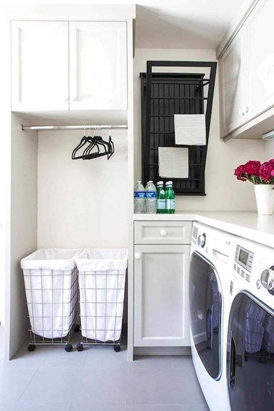 small laundry room with white wall, white tile, two machines, cabinets, white marble top, drying racks, hangers, laundry baskets