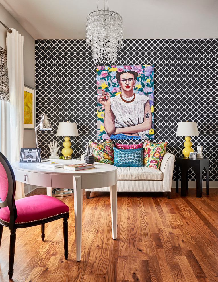 small writing desk with drawers artwork black and white wallpaper white curved desk pink chair wooden floor sofa colorful pillows table lamps black side tables window
