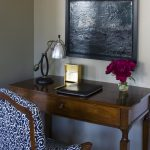Small Writing Desk With Drawers Black Artwork Wooden Desk Blue And White Chair Glass Flower Vase Industrial Table Lamp
