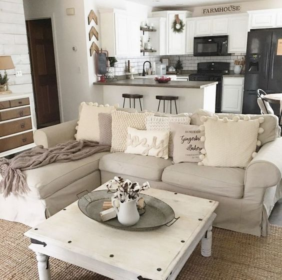 soft beige open space with white cabinet kitchen with dark top counter, beige sofa, brown rug, white wooden coffee table