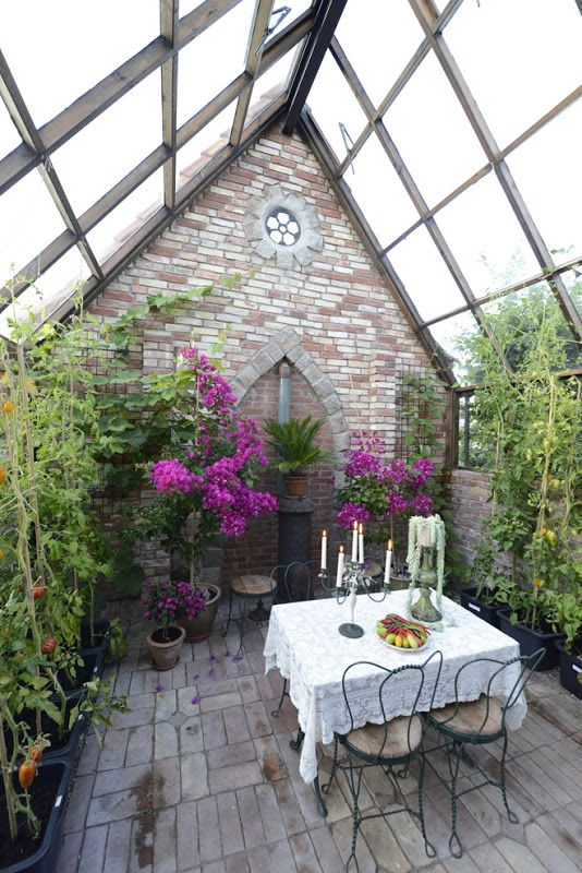sunroom with open brick wall and floor, plants, purple flowers, glass ceiling, black metal dining set with white clothe