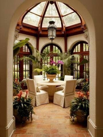 sunroom with round shape, orange tiles floor, beige wall, dark brown framed windows and ceiling, doom ceiling, white round dining set