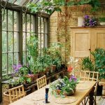 Sunroom With Wooden Floor, Open Brick Wall, Ceiling And Wall Of Clear Glass, Plants, Wooden Dining Set