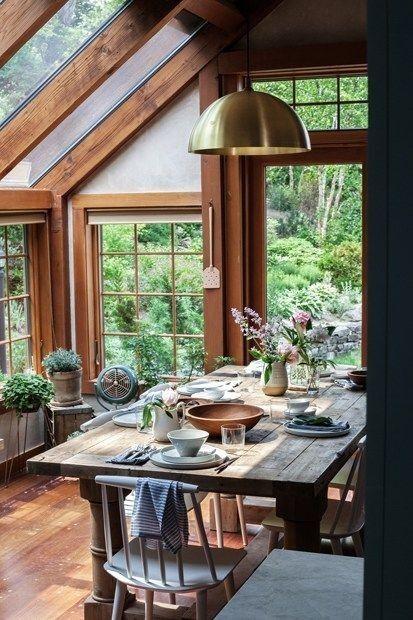 sunroom with wooden floor, wooden framed windows and door, wooden table and  chair, ceilign lamp, glass roof and windows