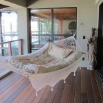Swing Hammock Bed Wooden Flooring Glass Windows Statue Stainless Steel Cable Deck Railing Wooden Railing Cap Tan Walls Sliding Glass Doors