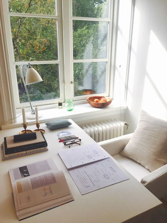 tall slide windows with white wooden table on side, white plushed chair