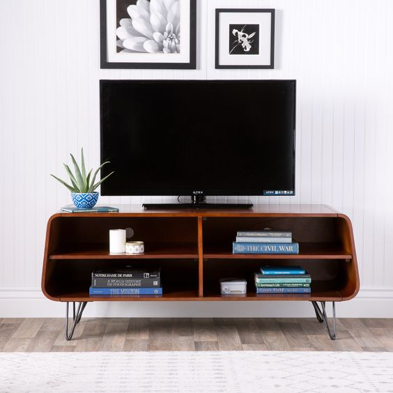 TV on the tv cabinet with shelves for books, metal legs