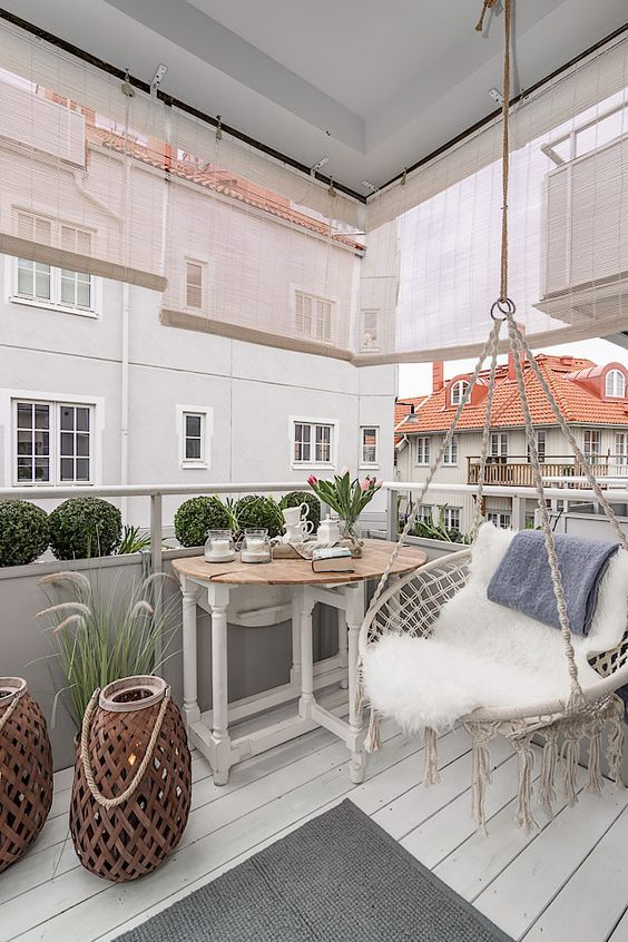 a balcony with white wooden floor, adjusted wooden table, round swing, shade