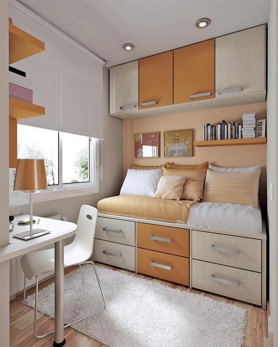 a bedroom with awrm brown in wooden floor, platform bed with drawers and cupboards, shelves, but white table