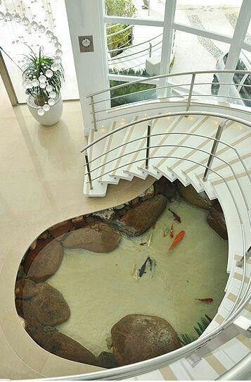 a medium sized pond inside the house under the stairs with nude base, beige tiles around