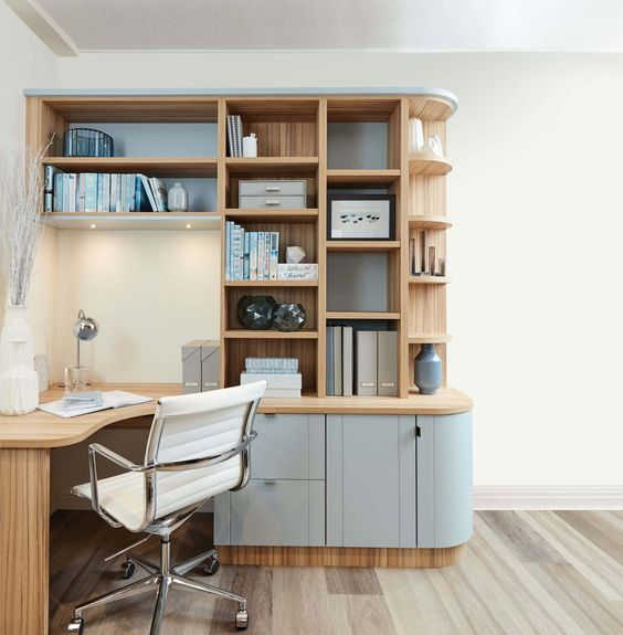 a modern study with wooden floor, wooden table built in with wooden shelves beside, white chair